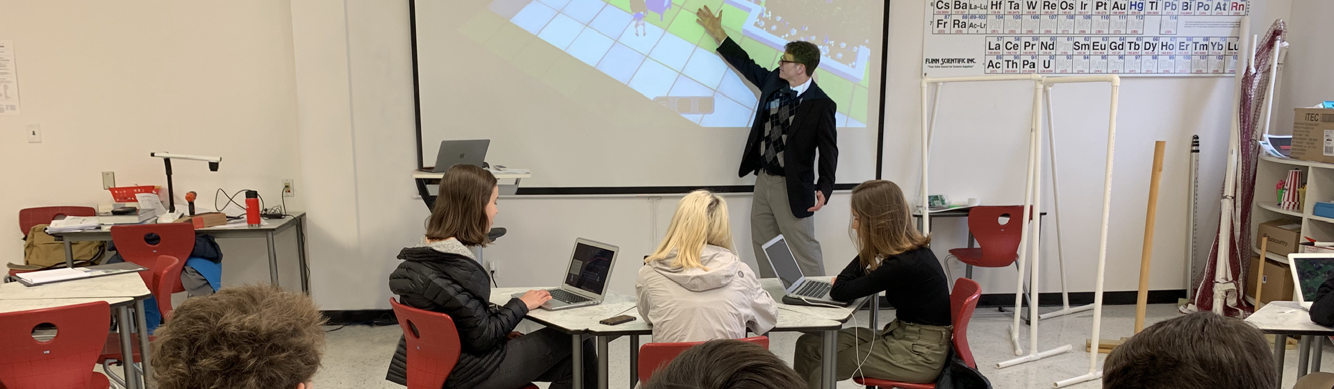 Well-dressed high school teacher demonstrates Plasma Games' Sci-Ops: Global Defense to teach chemistry concepts to his classroom